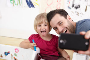 Father and daughter taking selfie with smart phone